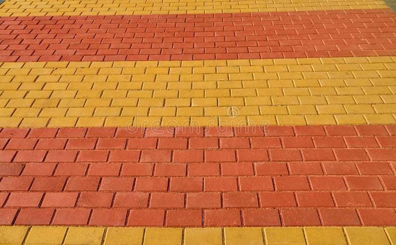 Yellow and red brown paving tile for background or texture stock image
