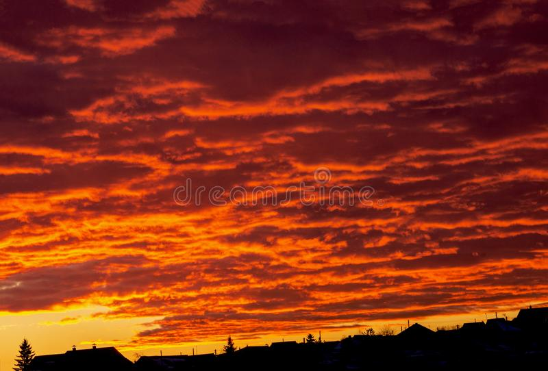 Yellow-red fiery, blazing like a flame the evening sky. Beautiful red-yellow sunset over the outlines of the city with clouds. stock photography