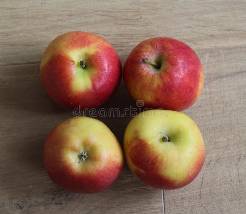 Yellow and red fresh Dutch jazz apples on wooden background royalty free stock images