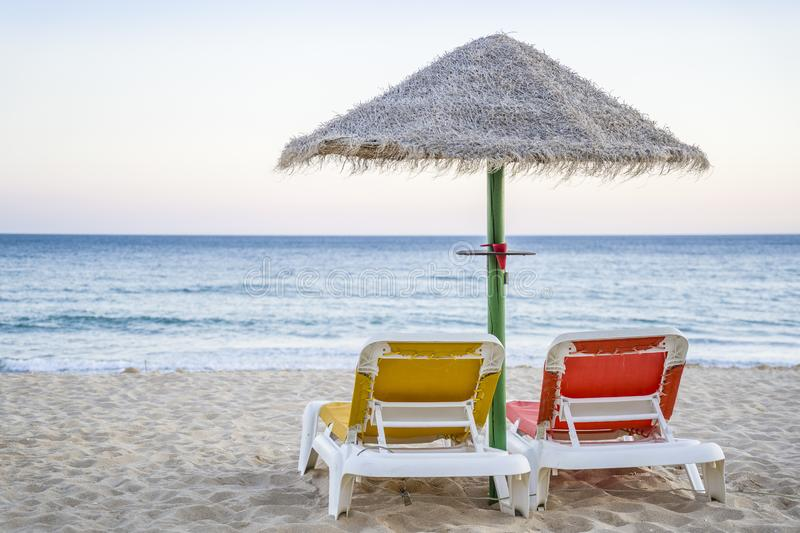 Yellow and red sun beds on the beach by sunset in Algarve, Portugal royalty free stock images