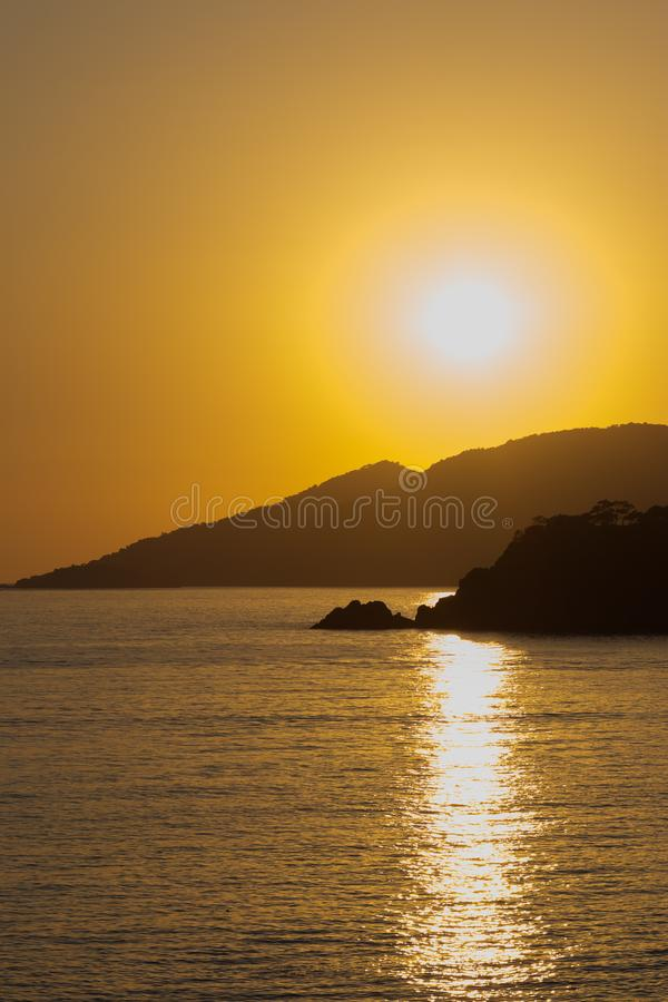 Yellow-red sunset over the island and the calm sea. royalty free stock photo