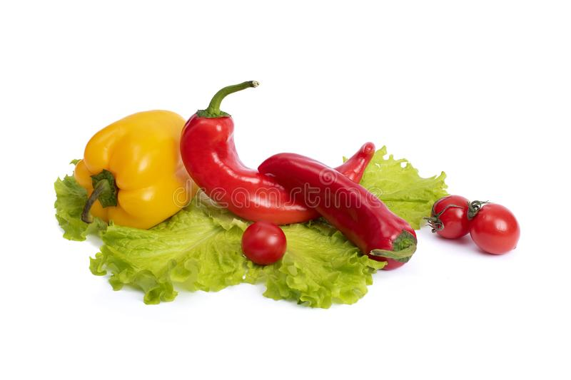 Yellow and red sweet pepper with tomatoes. Red sweet long pepper with yellow sweet pepper and tomatoes on a white background. Comp. Osition of yellow and red royalty free stock photography