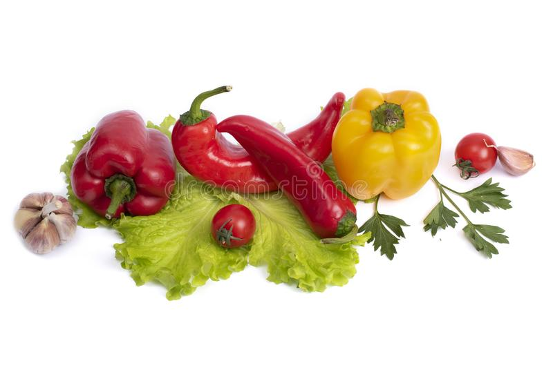 Yellow and red sweet pepper with tomatoes. Red sweet long pepper with yellow sweet pepper and tomatoes on a white background. Comp. Yellow and red sweet pepper royalty free stock images