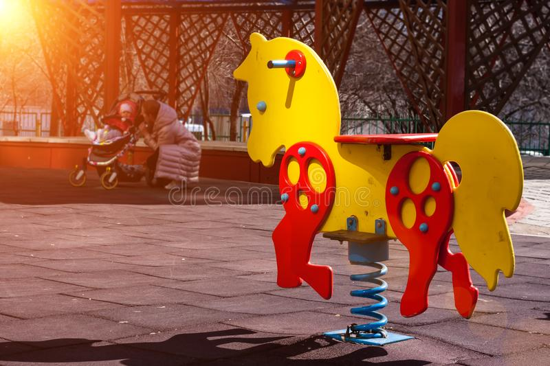 Yellow with red swing spring horse toy for kids on a children`s playground. Mother with baby in stroller at the background stock photo