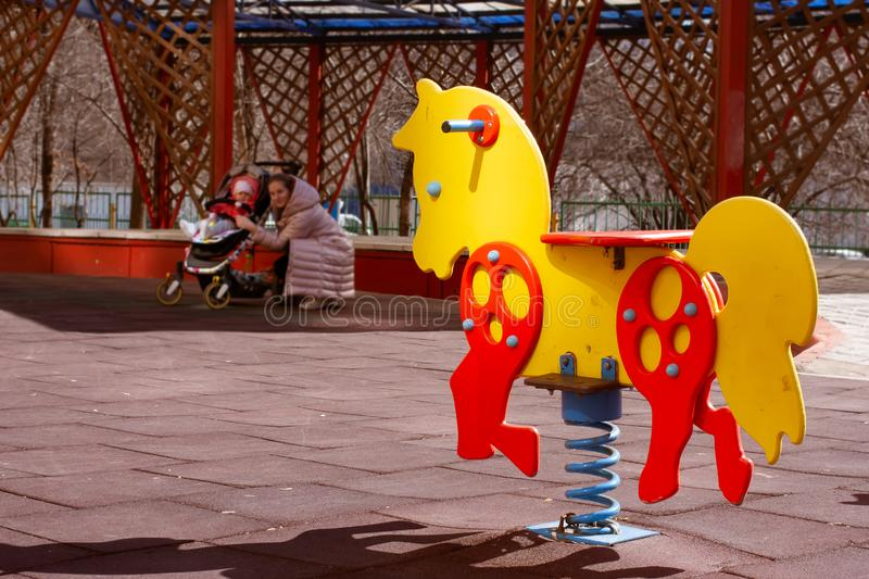 Yellow with red swing spring horse toy for kids on a children`s playground. Mother with baby in stroller at the background looks stock photos