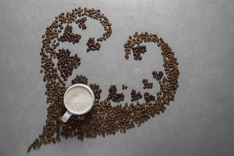 Coffee beans in the shape of a heart with a coffee cup stock images