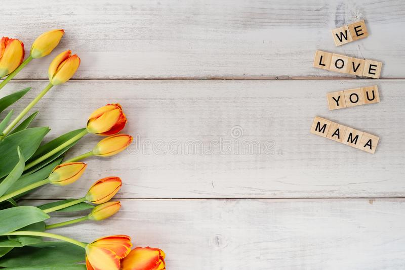 Yellow and red tulips on whitewashed wood with Mother`s Day mess. Age in letter tiles stock photography