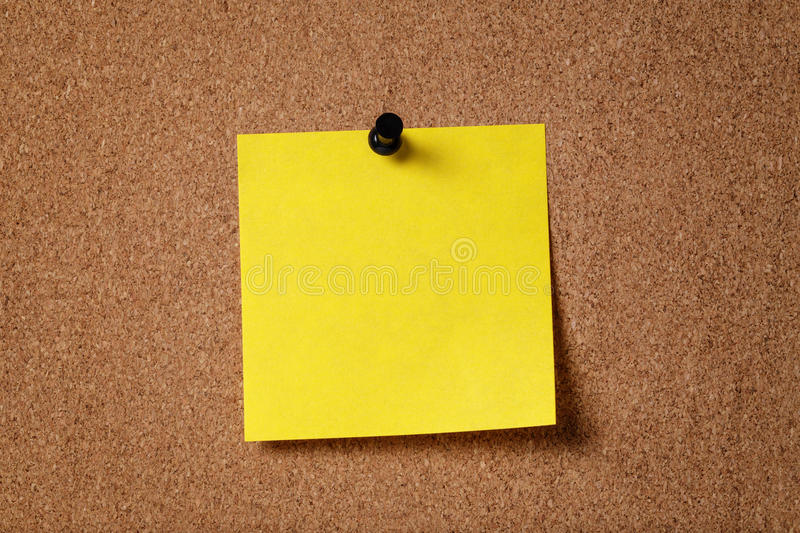 Yellow reminder sticky note on cork board royalty free stock images