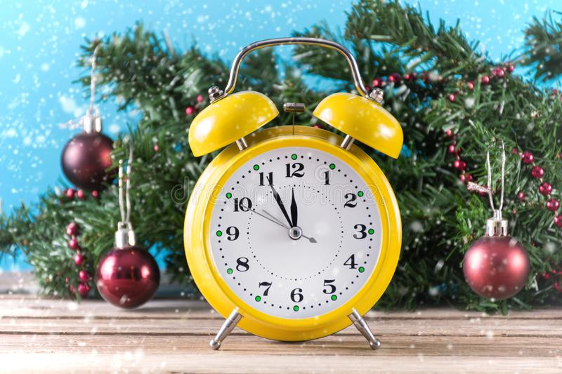 Yellow retro clock on wooden desk and fir Christmas tree with red ball decoration stock images