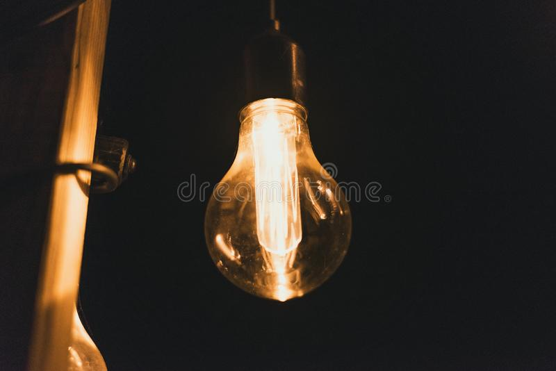 Yellow retro incandescent bulbs hang in the evening at a party. Light bulbs hanging on a wooden bridge at night.  royalty free stock image