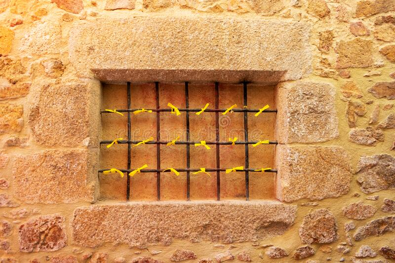Yellow ribbon displayed on prison bars as a symbol of solidarity and in support of jailed Catalan independence leaders and. Politicians stock photos