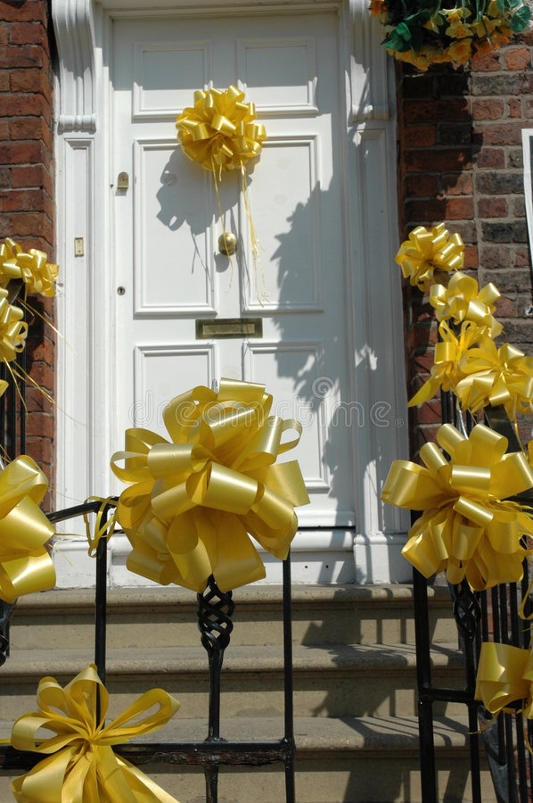 Yellow ribbons on white door stock photography