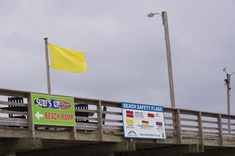 A Yellow Rip Tide Warning waves over the Bouge Inlet Pier royalty free stock images