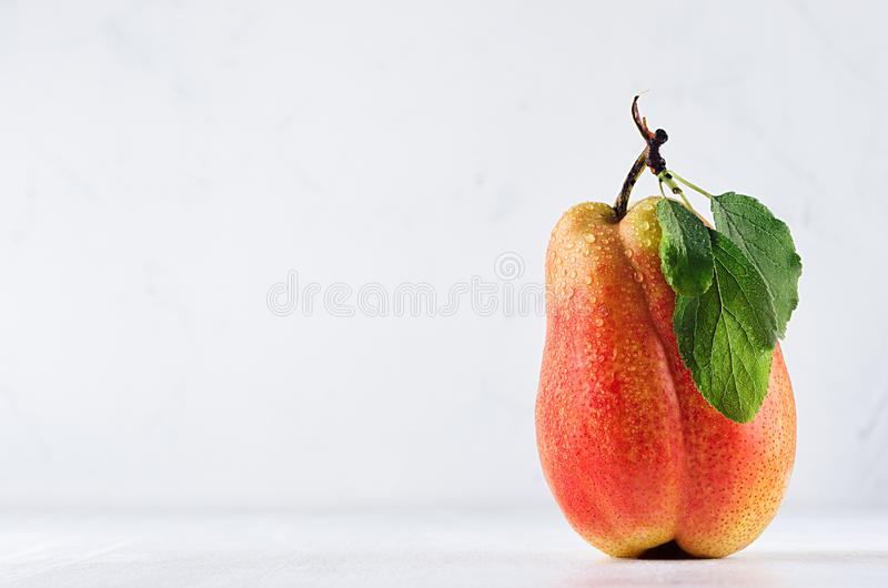 Yellow ripe pear with red side, green leaves and water drops on soft light white wood background. Healthy food backdrop. stock photos