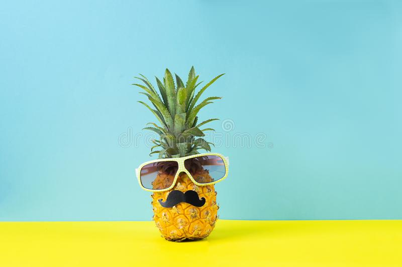 Yellow ripe pineapple in sunglasses with black mustache yellow blue background. Funny face from tropical fruit. Concept stock photography