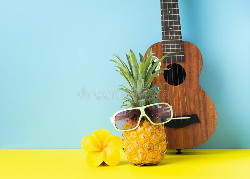 Yellow ripe pineapple in sunglasses. Guitar on yellow blue background. Funny muzzle of a tropical fruit. Party concept. stock photography