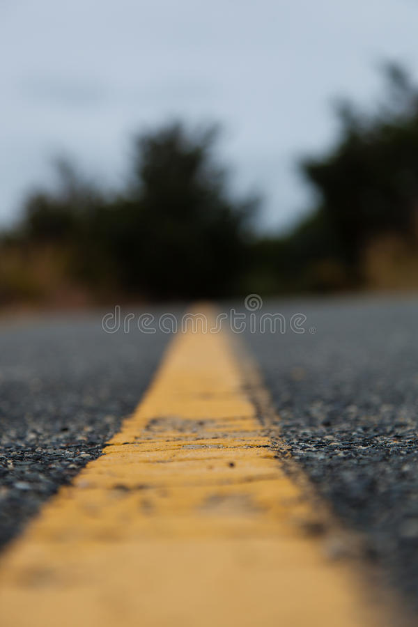 Yellow Road Line Closeup. Road Closeup with Yellow Line; blurry in foreground and background; vertical image; dismal day royalty free stock photo