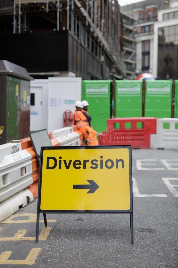 Yellow Road Sign with Arrow, Diversion: Barrier and Workers in background.  stock photos