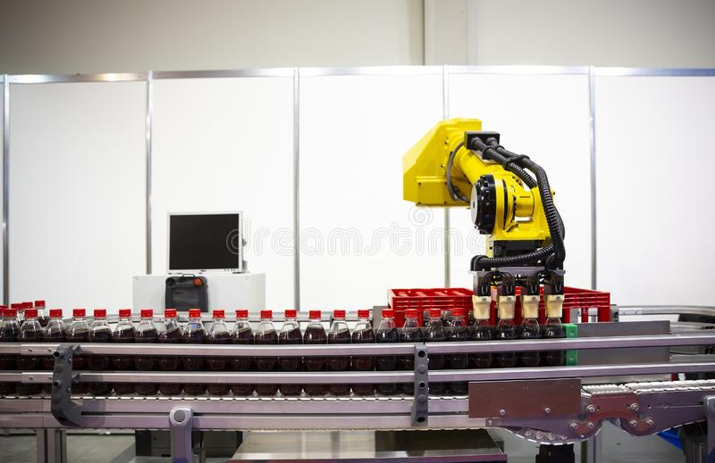 Yellow robotic arm soda bottles. Yellow robotic arm arranges plastic soda bottles in ? packing case. Automatic industrial machinery equipment royalty free stock photo
