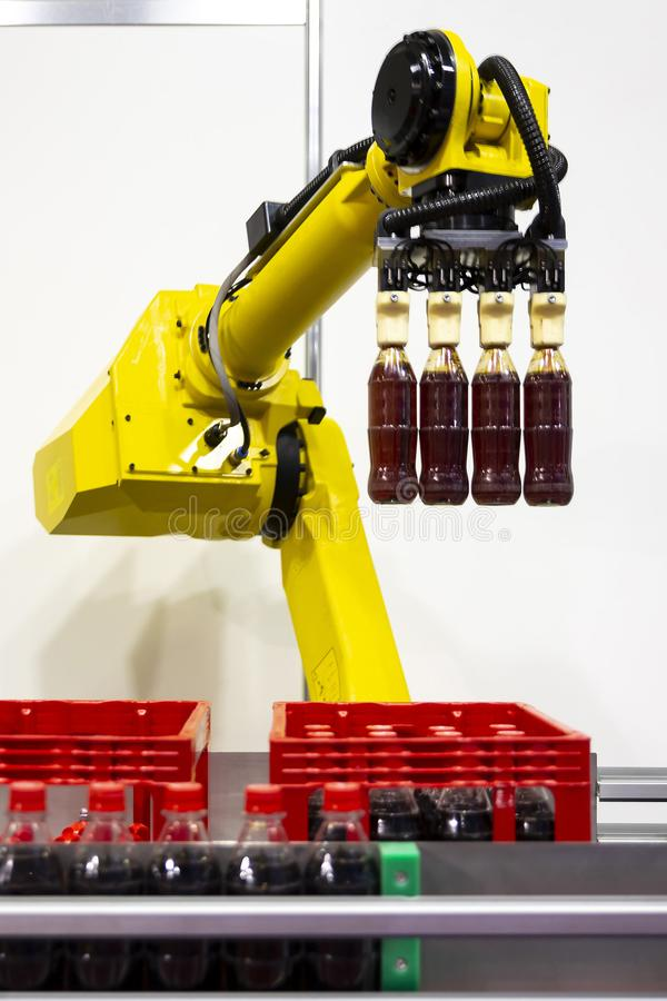 Yellow robotic arm soda bottles. Yellow robotic arm arranges plastic soda bottles in ? packing case. Automatic industrial machinery equipment. Vertical stock photography