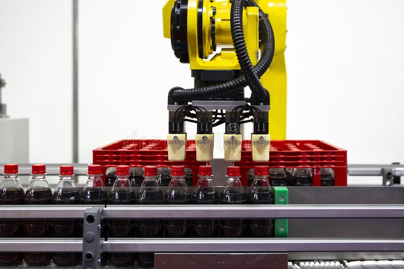 Yellow robotic arm soda bottles. Yellow robotic arm arranges plastic soda bottles in ? packing case. Automatic industrial machinery equipment royalty free stock image