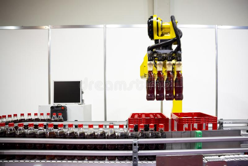 Yellow robotic arm soda bottles. Yellow robotic arm arranges plastic soda bottles in ? packing case. Automatic industrial machinery equipment stock photos
