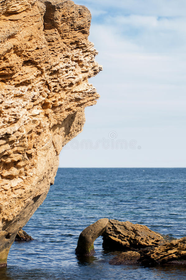 Yellow rock in the blue sea stock image