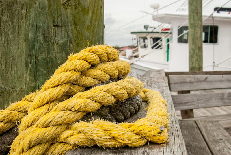 Yellow Rope Wrapped Around Post on Pier. Tightly woven yellow rope wrapped around a post on a boat dock royalty free stock images