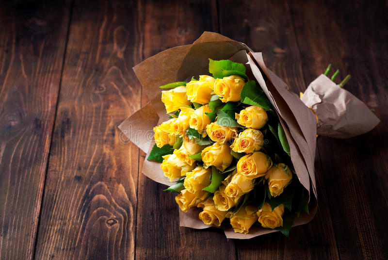 Yellow roses bouquet. In kraft paper on a wooden background, selective focus royalty free stock photos