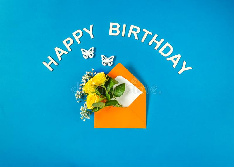 Yellow roses and Gypsophila in envelope and butterflies on cyan background. Text Happy Birthday. Top view, flat lay. stock photo