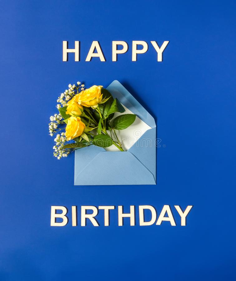 Yellow roses and white Gypsophila in blue envelope close-up on blue background. Text Happy Birthday. Top view, flat lay. stock image