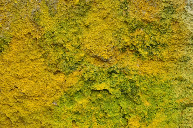 Yellow rough background. Rough deteriorated cement wall airbrushed with yellow and green graffiti paint stock image