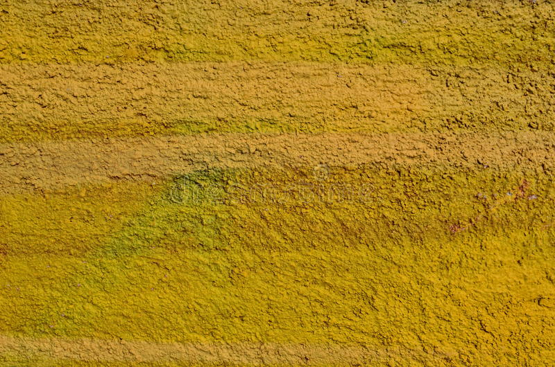 Yellow rough plaster. Rough plastered wall airbrushed with yellow paint stock photography