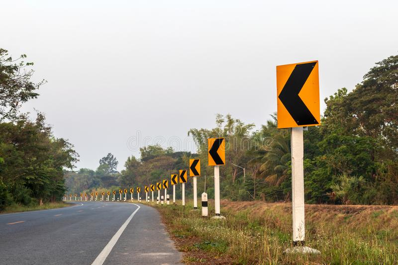 Yellow row signs, curves on the road. Low view of the row of signs, yellow curves on Thai roads in the daytime, near the forest stock images