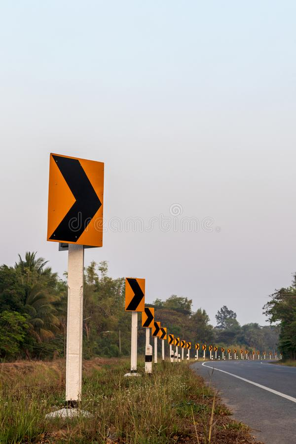 Yellow row signs, curves on the road. Low view of the row of signs, yellow curves on Thai roads in the daytime, near the forest stock photo