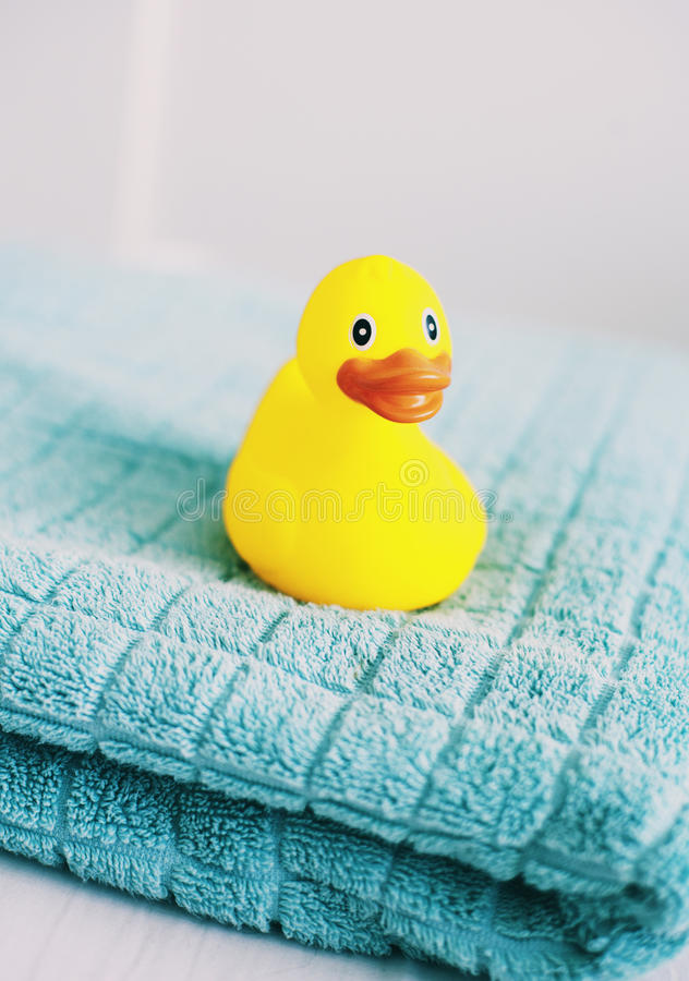 Yellow rubber duck. Cute rubber duck on a towel in bathroom stock image