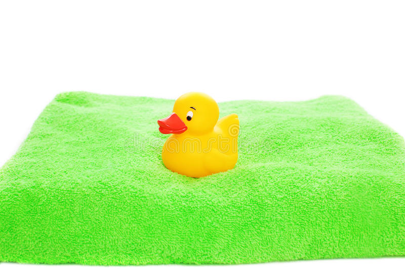 Yellow rubber duck toy and green towel. Isolated on a white background stock photography