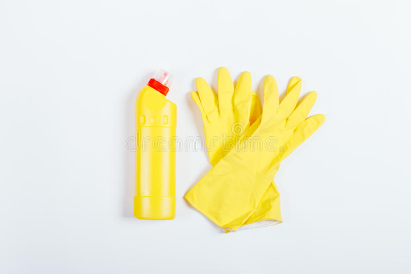 Yellow rubber gloves and a bottle of detergent on white background. Top view stock photos