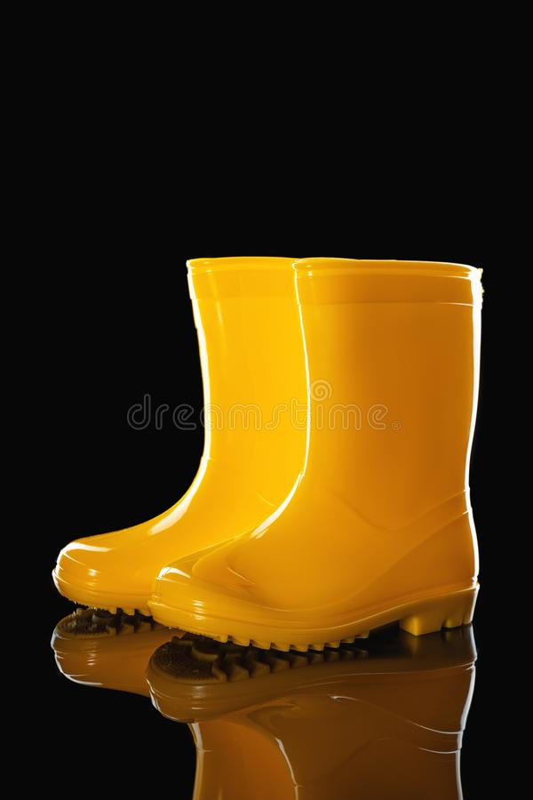 Yellow Rubber Rain Boots for kids isolated on black background stock images