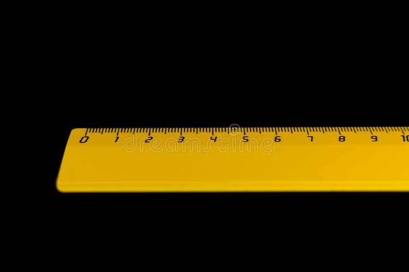 Yellow ruler on a black background 10 centimeters.  stock photo