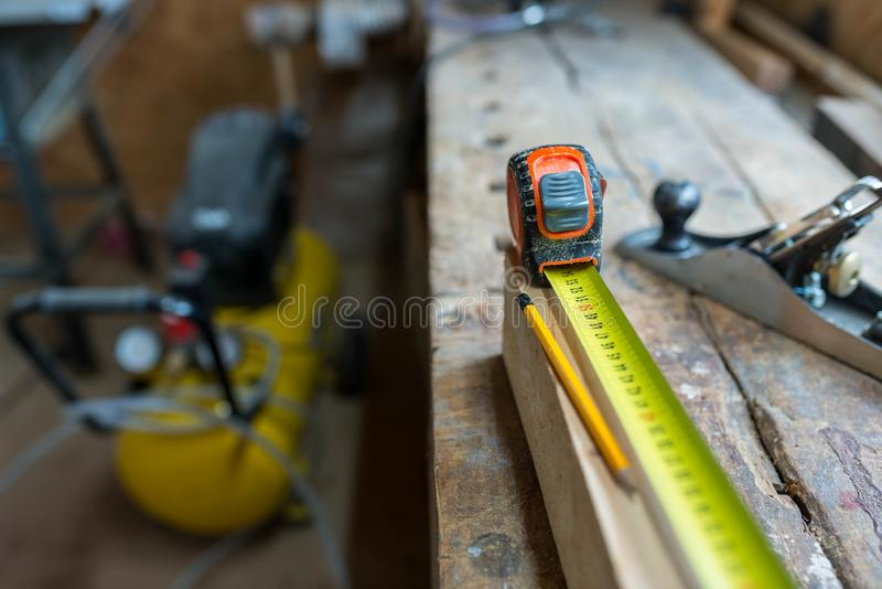 Yellow ruler , pencil on pine wood board, cracked old oak workbench royalty free stock photography