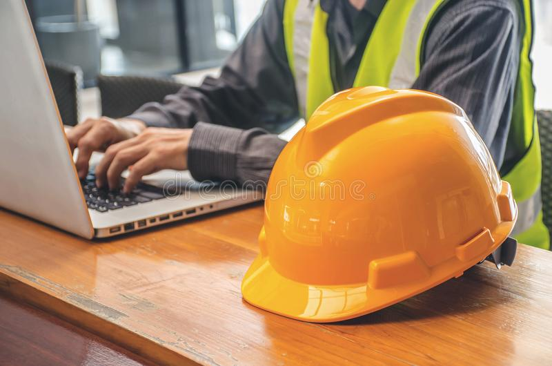 The yellow safety helmet and Business man in Construction industry is working in on computer. stock images