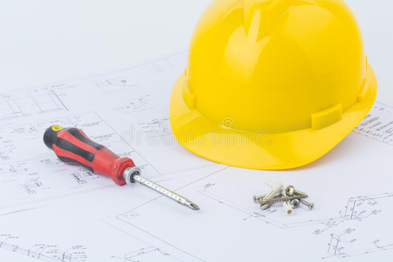 Yellow safety helmet and screwdriver. On structure plan background royalty free stock image