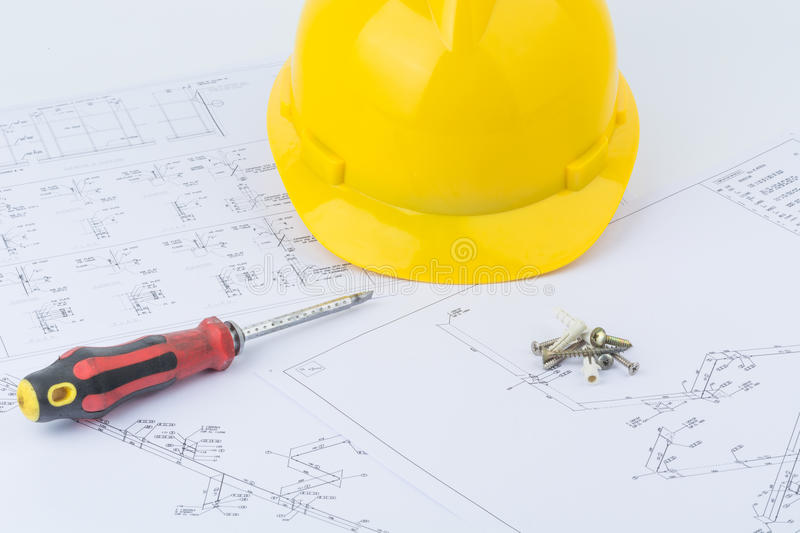 Yellow safety helmet and screwdriver. On structure plan background stock photos
