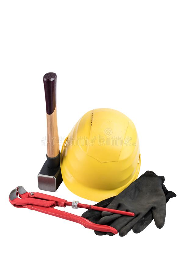 Yellow safety helmet with a sledgehammer with wooden handle, working gloves and adjustable plumbers wrench isolated on a white bac stock photo