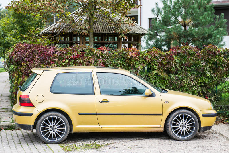 Yellow saloon car. Closeup of yellow hatchback saloon car with alloy wheels parked beside ivy covered fence on designated area stock photos