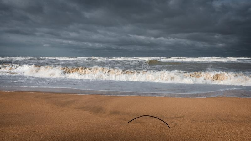 Yellow sand on an empty beach, stormy sea. Overcast weather royalty free stock photo