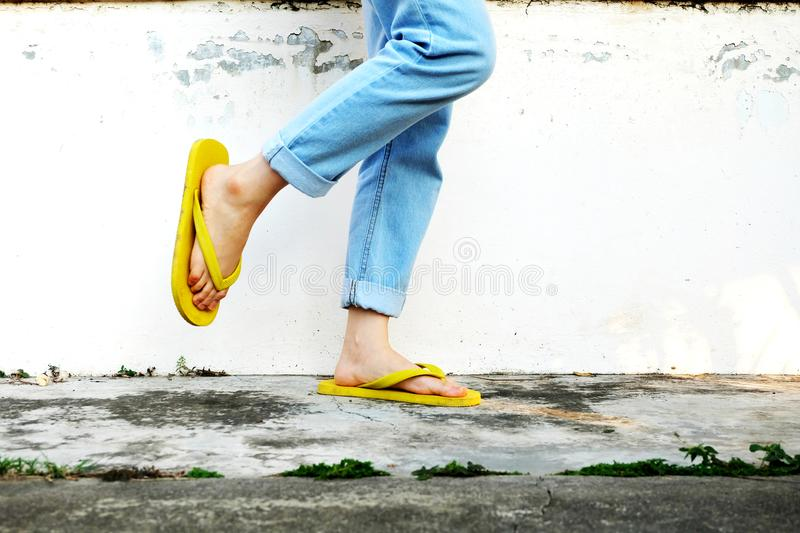 Yellow Sandals. Woman Wearing Flip Flops and Blue Jeans Standing on Old Cement Floor stock images
