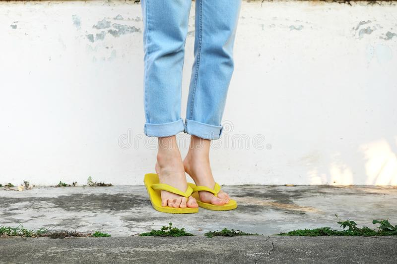 Yellow Sandals. Woman Wearing Flip Flops and Blue Jeans Standing on Old Cement Floor. Background Great for Any Use stock photos