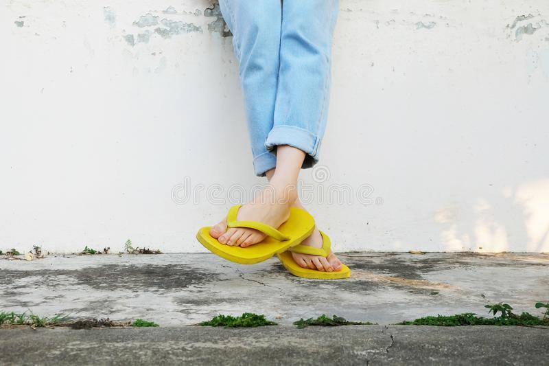 Yellow Sandals. Woman Wearing Flip Flops and Blue Jeans Standing on Old Cement Floor. Background Great for Any Use stock photo